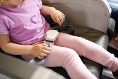 Das kleine Mädchen sitzt in einem Passagierstuhl des Flugzeugs stockfoto