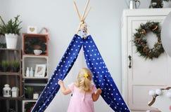 Das kleine Mädchen spielt in einem kleinen Wigwam Stockfotos