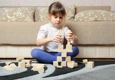 Das kleine Mädchen spielt hölzerne Spielzeugwürfel Stockbild