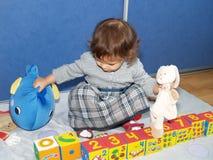 Das kleine Mädchen spielt mit den Würfeln und sitzt auf einem Boden Lizenzfreie Stockfotografie