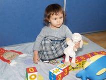 Das kleine Mädchen spielt mit den Würfeln und sitzt auf einem Boden Stockbilder