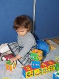 Das kleine Mädchen spielt mit den Würfeln und sitzt auf einem Boden Stockfotografie