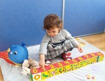 Das kleine Mädchen spielt mit den Würfeln und sitzt auf einem Boden Stockfoto
