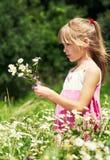 Das kleine Mädchen stanging in der Wiese Lizenzfreies Stockfoto