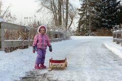 Das kleine Mädchen trägt Schlitten im Winterschneewald Stockbild