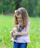 Das kleine Mädchen umfasst ein Kaninchen in einem Sommergarten Stockbilder