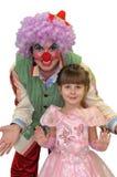 Das kleine Mädchen und der Clown. Stockbild