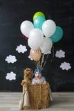 Das kleine Mädchen und der Schoßhund, die in einem Korb des Ballons sitzen Stockfotografie