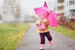 Das kleine Mädchen unter einem Regenschirm im Fall Stockfotos