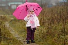 Das kleine Mädchen unter einem rosa Regenschirm im Fall Stockbilder