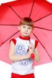 Das kleine Mädchen versteckt unter dem Regenschirm Stockfotos