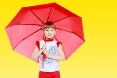 Das kleine Mädchen versteckt unter dem Regenschirm Stockfoto