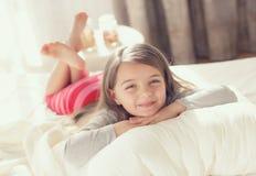 Das kleine Mädchen wachte auf und legt in Bett Lizenzfreies Stockbild