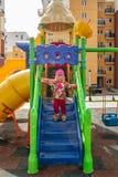 Das kleine Mädchen, warm gekleidet, in den Spielen eines Hutes und der Jacke auf dem Spielplatz mit Dias und Schwingen im Hof von lizenzfreie stockfotos