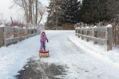 Das kleine Mädchen zieht den Schlitten im Winterschneewald Lizenzfreie Stockfotos