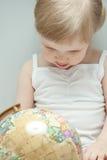 Das kleine Mädchen, das eine Kugel überprüft Lizenzfreies Stockfoto
