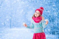 Das kleine Mädchen, das mit Spielzeugschnee spielt, blättert im Winterpark ab Lizenzfreies Stockfoto