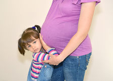 Das kleine Mädchen umfasst Hände ein Magen der schwangeren Mutter Stockfotografie