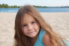 Das kleine nette kleine Mädchen, reizend, sitzt auf dem Strand, Porträt Stockfoto