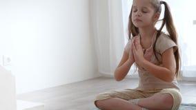 Das kleine nette Mädchen, das in der Yogalotoshaltung sitzt und meditiert nahe dem Fenster stock video