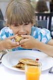 Das kleine nette Mädchen sieben Jahre alt essen Pfannkuchen. lizenzfreies stockfoto