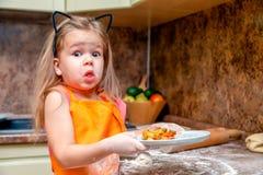 Das kleine schöne nette Mädchen im orange Schutzblech lächelnd und selbst gemachte Pizza machend, rollen die Küche des Teigs zu H lizenzfreie stockfotos
