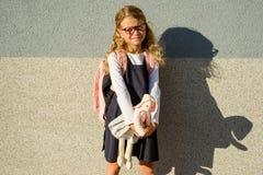 Das kleine Schulmädchen nahm ihr Spielzeug zur Schule mit ihr Stockfotografie