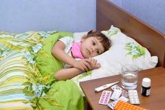 Das kleine traurige kranke Mädchen liegt in einem Bett Lizenzfreie Stockbilder