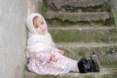 Das kleine traurige Mädchen in einem weißen Schal sitzt Lizenzfreie Stockfotografie