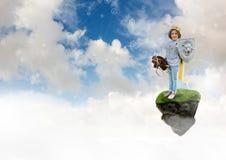 Das Kleinkind, das als Ritter spielt auf sich hin- und herbewegender Rockplattform im Himmel mit Verbindungsstücken gekleidet wir Stockfotografie