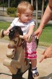 Das Kleinkind, das auf Pferd spielt, tetter-totter Stockbild