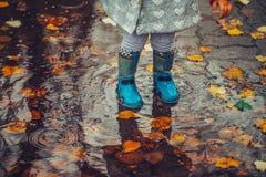 Das Kleinkind springend in Wasserbecken am Herbsttag stockfotografie