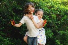 Das Kleinkindumarmen, ihre Gesichter und Hände werden gefärbt Stockfotografie