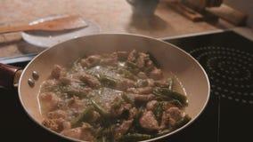 Das Kochen cicken mit Bohnen auf der Wanne stock video footage