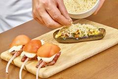 Das Kochen, das Lebensmittel, das oben vom Mann nah ist, übergibt den Reibkäse, der auf der angefüllten Aubergine besprüht wird Lizenzfreie Stockbilder