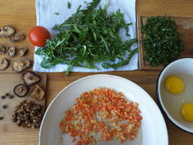Das Kochen des Löwenzahns lässt Omelett mit Pilzen Stockfotos