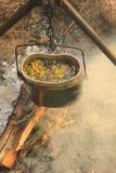 Das Kochen essen im Werfer auf dem Feuer Junge Erwachsene Stockbild