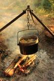 Das Kochen essen im Werfer auf dem Feuer Junge Erwachsene Lizenzfreies Stockfoto