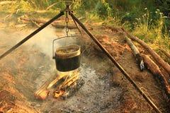 Das Kochen essen im Werfer auf dem Feuer Junge Erwachsene Lizenzfreie Stockfotos