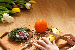 das Kochen, Hand schneidet Banane, Orange, gefrorene Erdbeerbrombeeren und Samen klare Smoothiebestandteile und Mischmaschine, Ju Stockfoto