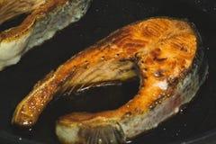 Das Kochen zwei briet Lachssteaks in der schwarzen Wanne stockbilder