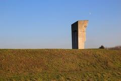 Das konkrete Monument auf dem Hintergrund des grünen Grases und des Himmels Lizenzfreie Stockfotos