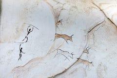 Das Konzept, das auf einem Felsen, alte Leute gemalt wird, jagen Tierbüffel mit einer Stange Stockbilder
