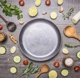 Das Konzept, das die vegetarischen Lebensmittelinhaltsstoffe ausgebreitet werden um die Wanne mit einem Messer kocht, würzt Raum  stockfotos
