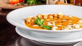 Das Konzept der italienischen Küche Kürbissahnesuppe mit orange Aroma, Hühnerstücken, Brotcroutons und Creme stockfoto