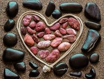 Das Konzept der Liebe Rötliche Seesteine, vereinbart in einem Herz sha Stockfotos