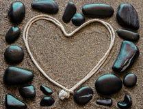 Das Konzept der Liebe Steine Schwarzen Meers vereinbarten um einen Rahmen, h Stockfotografie