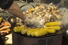 Das Konzept der Straßennahrung: gebratene Kartoffeln und Maiskolben, Dampf über einer Bratpfanne, Unschärfe lizenzfreies stockfoto