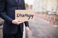 Das Konzept der Strategie Ein junger Gesch?ftsmann in einem Anzug h?lt ein Zeichen herein seine Hand lizenzfreie stockfotos