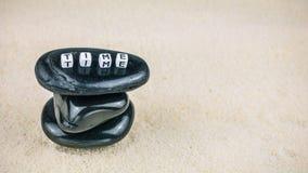 Das Konzept der Zeit SETZEN Sie Zeit Würfelbuchstaben auf dem schwarzen Stein fest, der Sandhintergrund schriftlich ist Lizenzfreie Stockfotografie